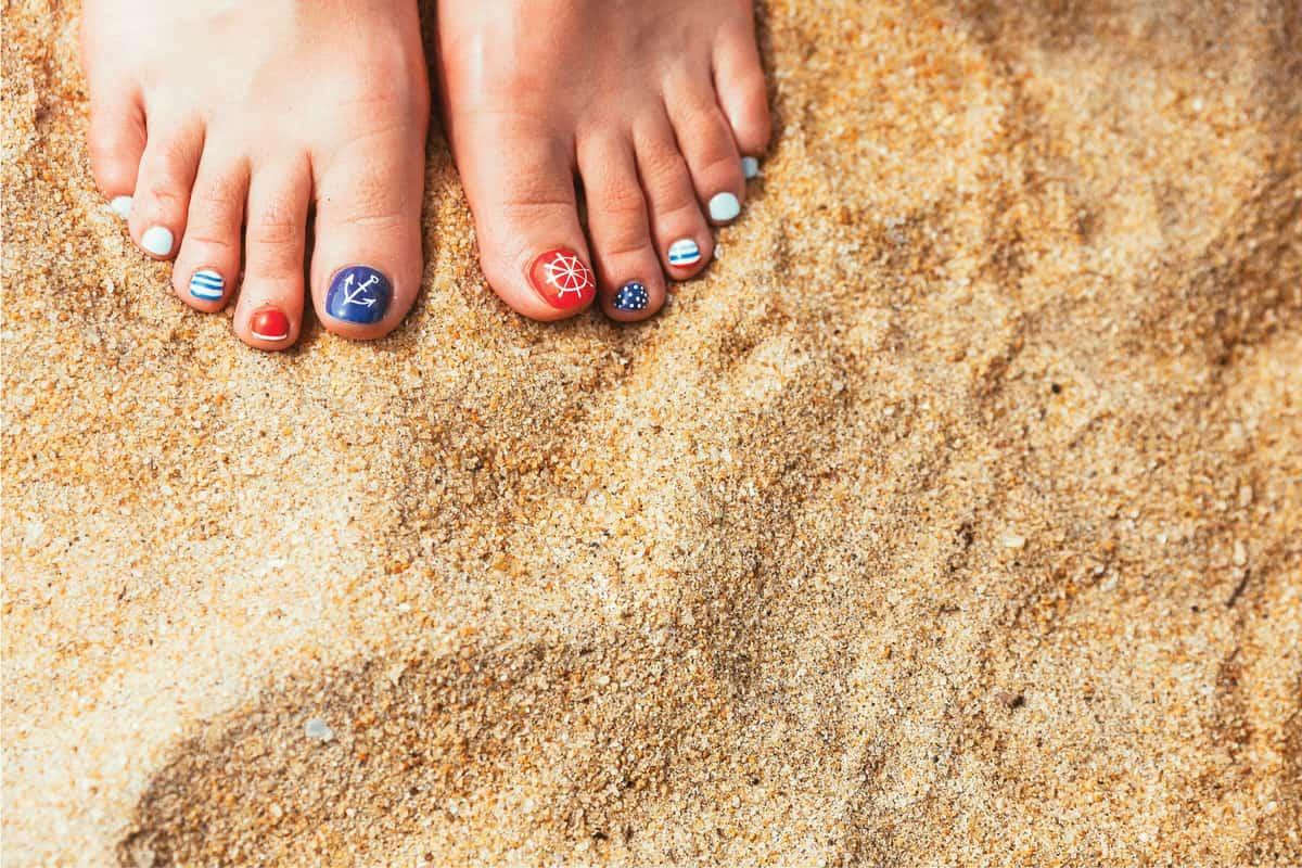 Female sea style pedicured feet on summer shore sand