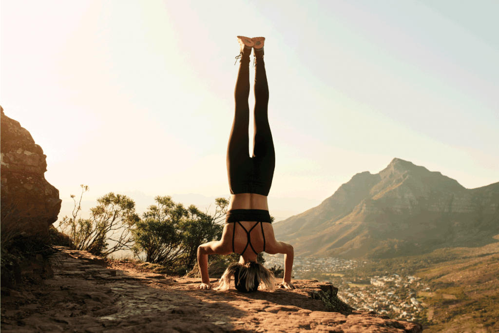 Full length shot of an unrecognizable young woman doing a handstand while hiking in the mountains. For What Can You Wear Yoga Pants