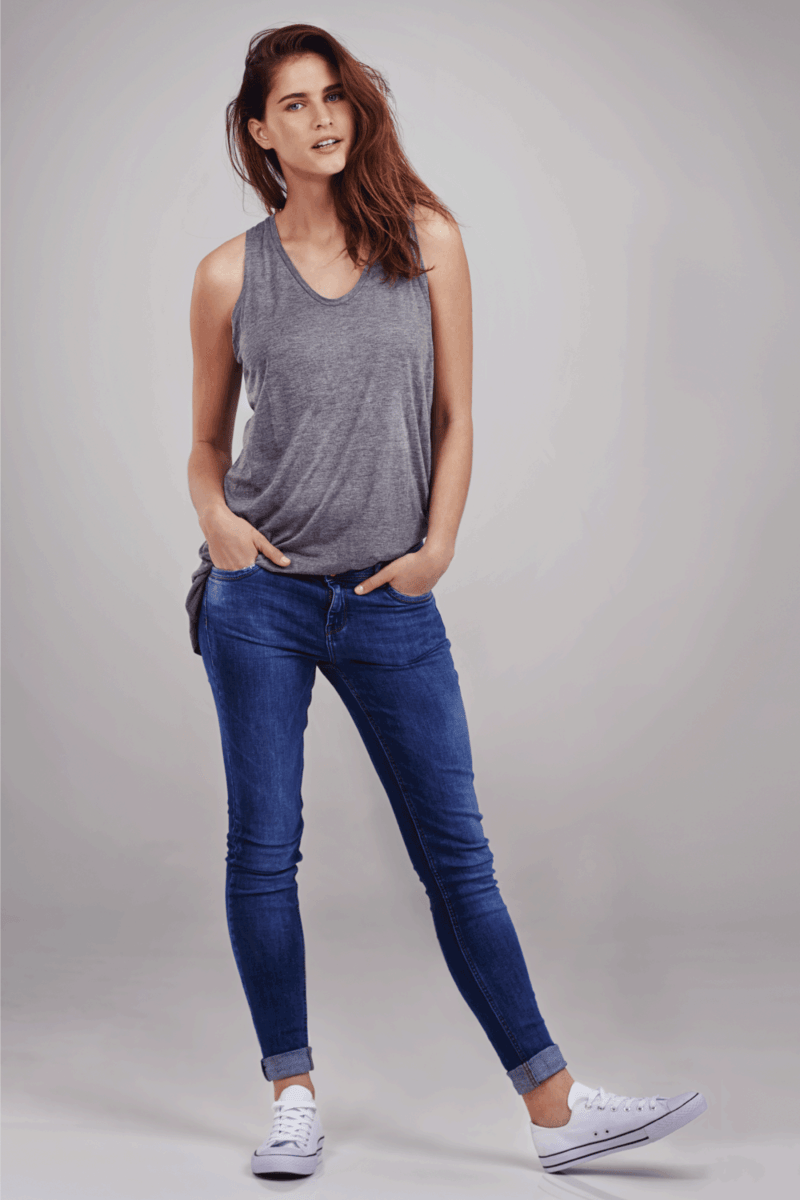 Full length studio portrait of casually-dressed young woman wearing jeans