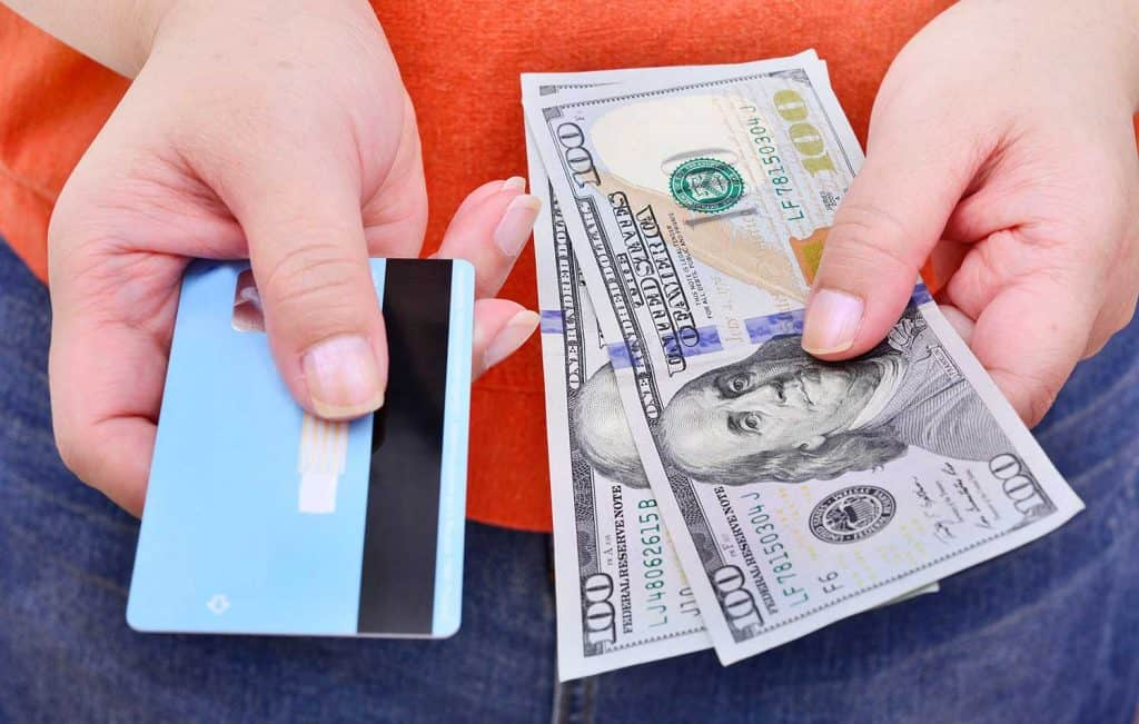 Hands holding US dollar bills and credit card