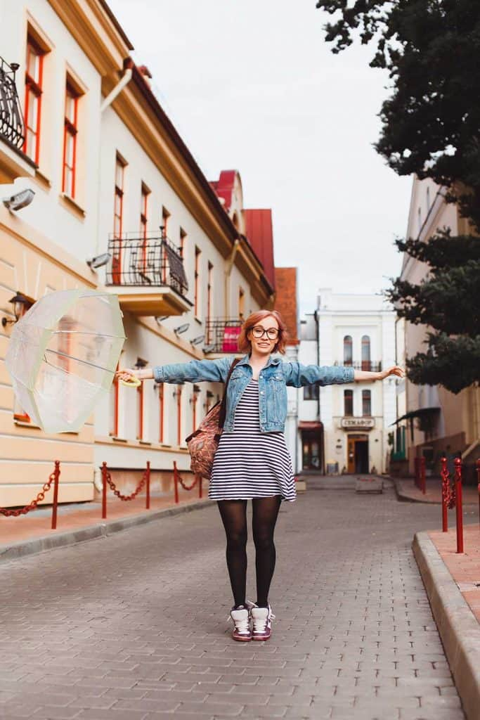 Hipster girl in striped dress and denim jacket posing on the street