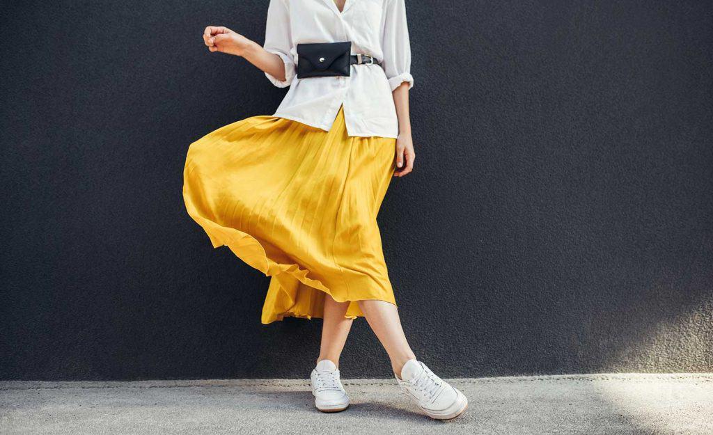 Horizontal cropped image of stylish slim woman in beautiful yellow skirt