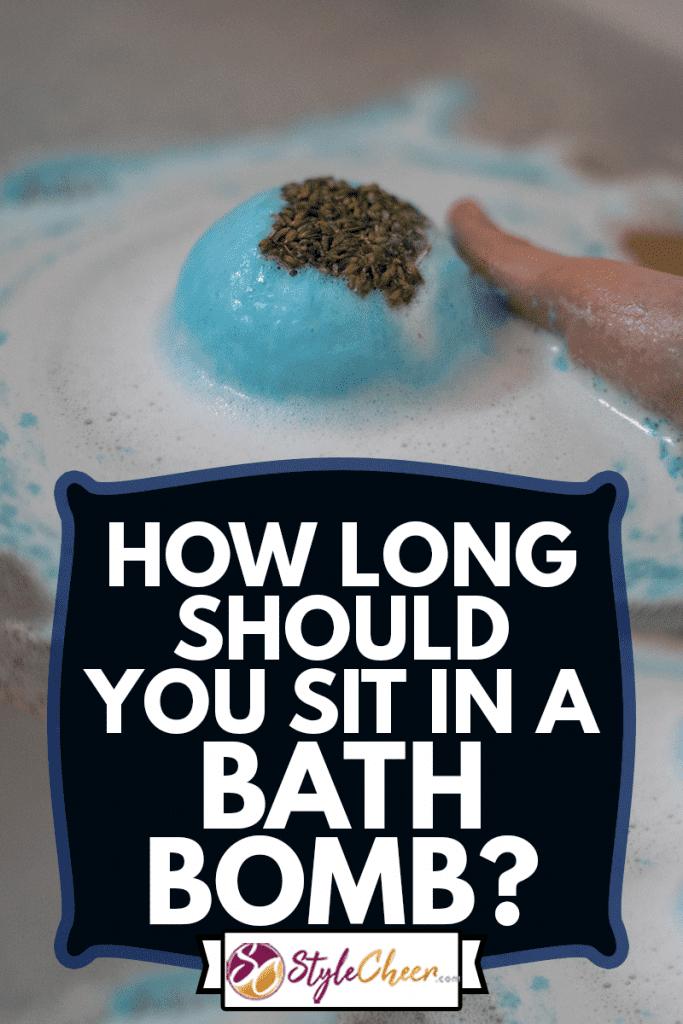 Hand taking a blue bath bomb dissolving in the bathtub, How Long Should You Sit In A Bath Bomb?