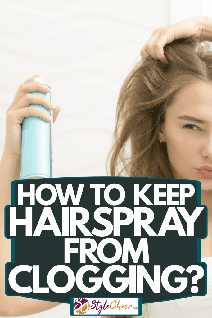 A beautiful blonde woman applying hairspray on her blonde hair, How To Keep Hairspray From Clogging
