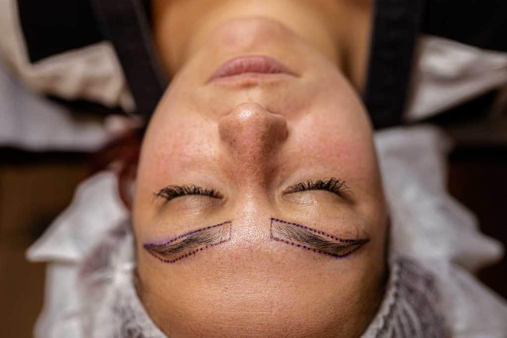 Make-up artist applying permanent make-up on eyebrows