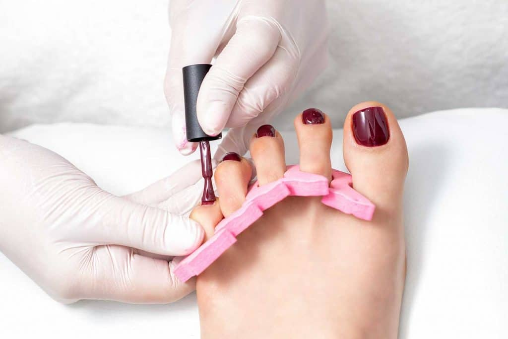 Manicure master painting on female toenails with maroon nail polish