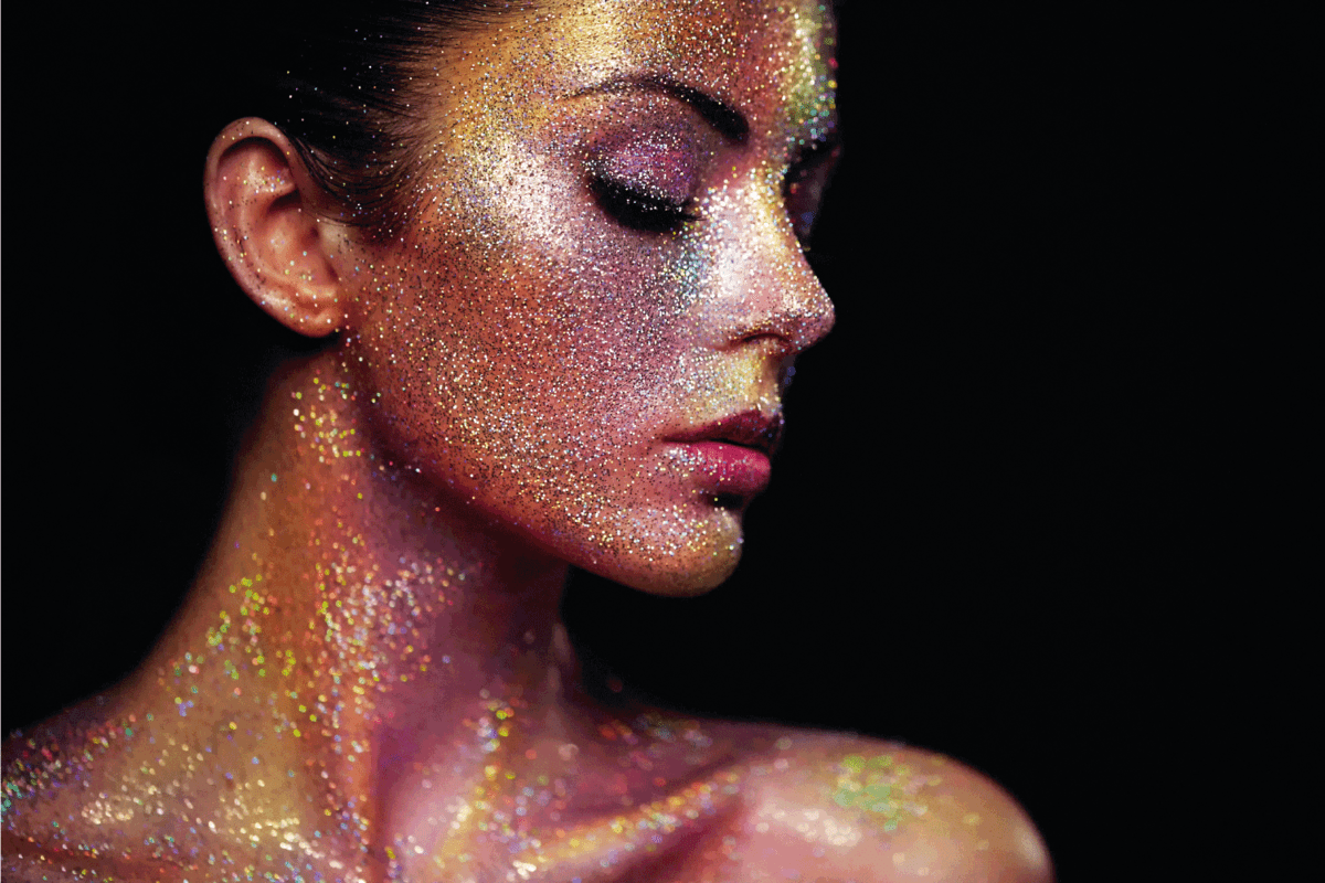 Portrait of Beautiful Woman with Sparkles on her Face. Girl with Art Make-Up in Color Light. Fashion Model with Colorful Makeup. How To Get Body Glitter To Stick