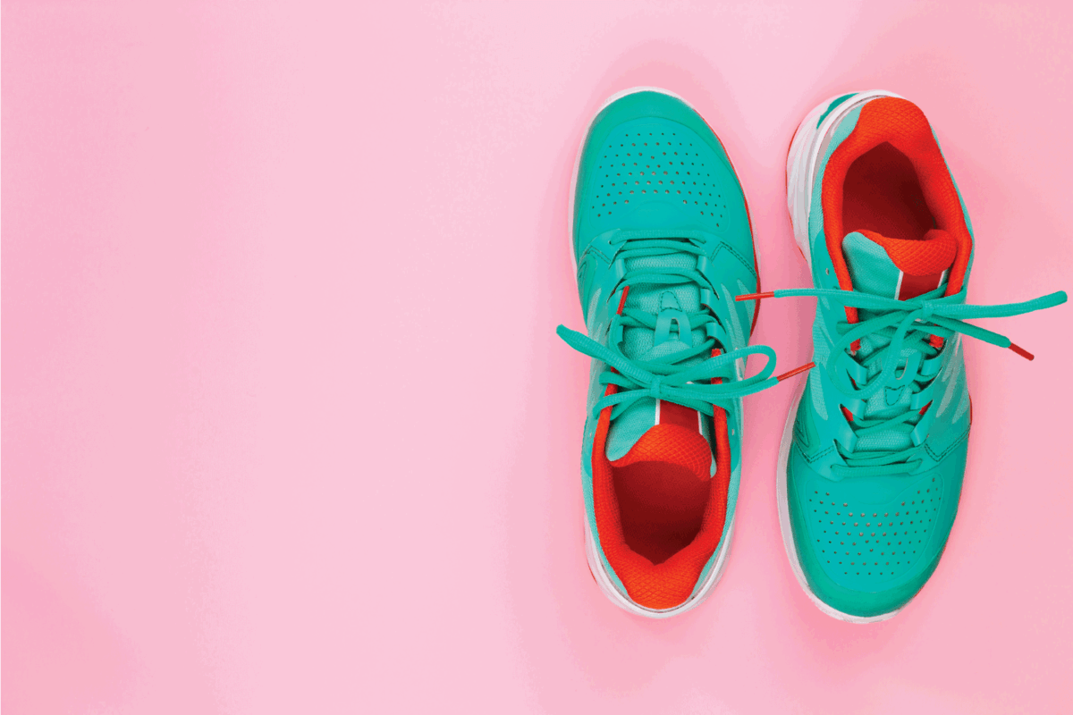 Red, cyan, white pair of new tennis shoes in studio shot over pink background