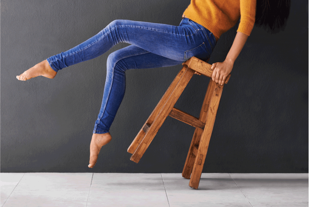 Shot of a happy young woman laughing while leaning back on a stool. How Long Should Skinny Jeans Be