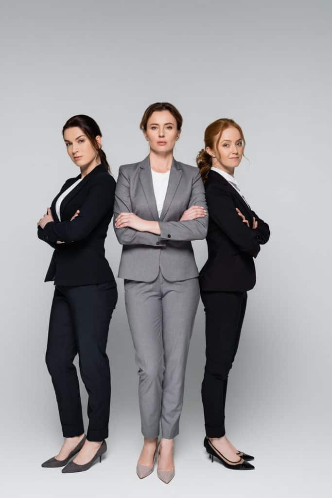 Three business women wearing gray and black suits on a gray background