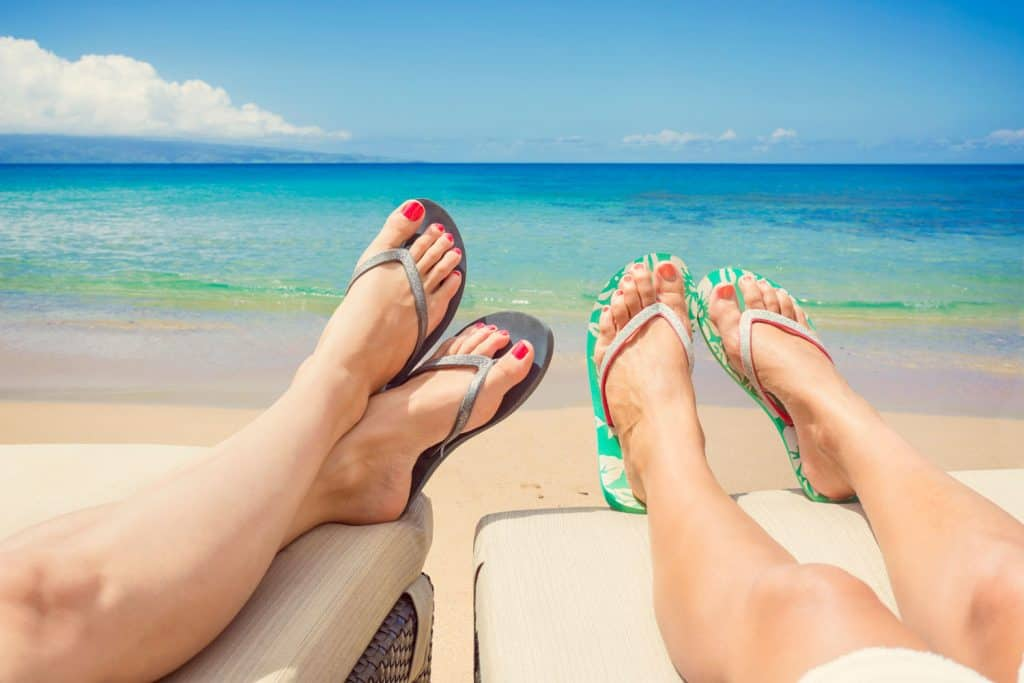 Two women wearing black and green flip flops and getting tan at the beach, How Should Flip-Flops Fit?
