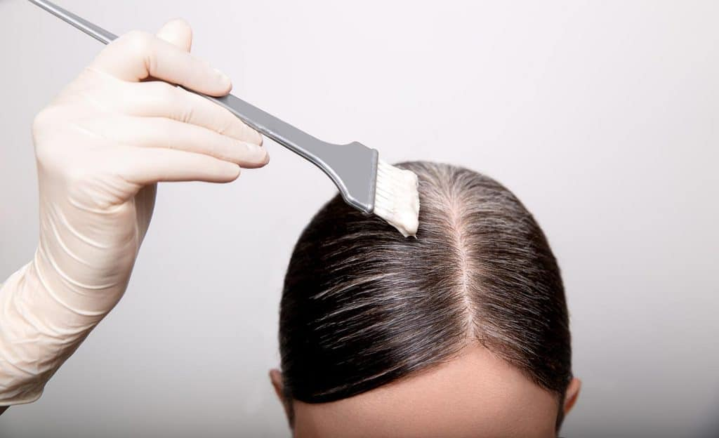 Woman dyeing gray hair root with brush and hair color