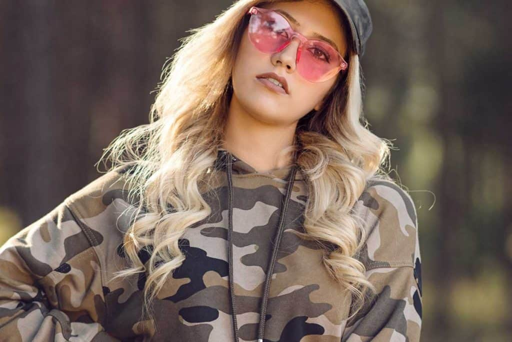 Woman wearing camo hoodie in the forest, What Color Lipstick Goes With Camo Outfits?