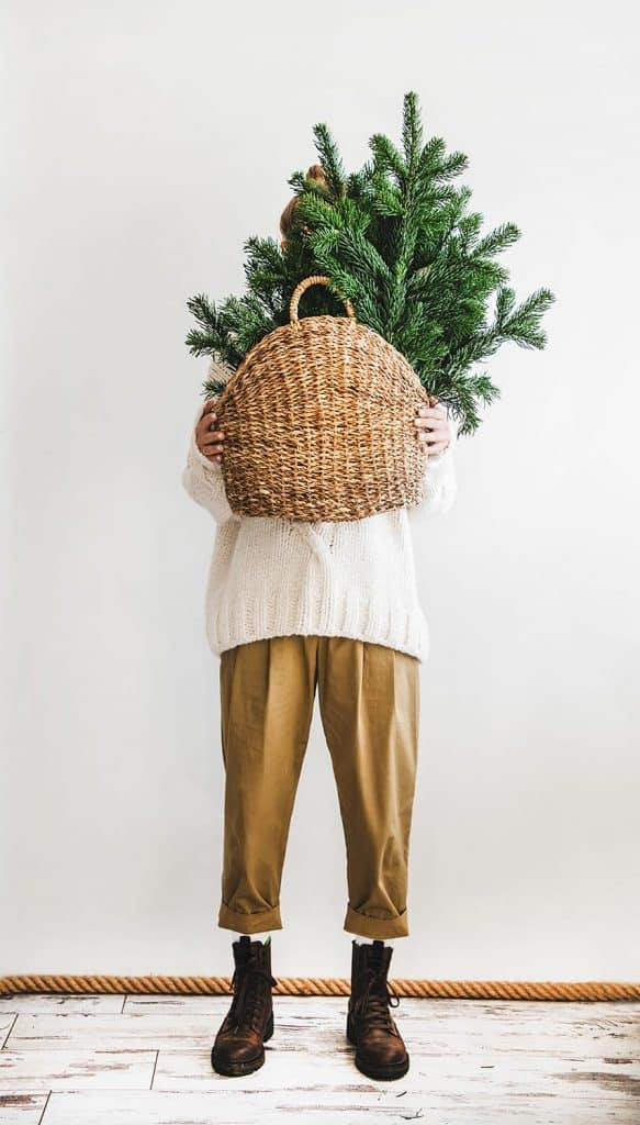 Woman wearing khaki pants and boots standing while holding wicker bag with evergreen Christmas tree branches