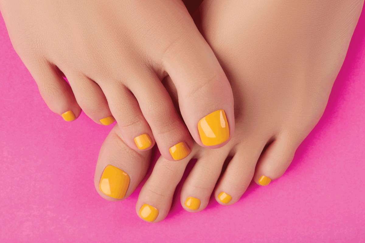 Womans feet with spring summer nail design on pink background