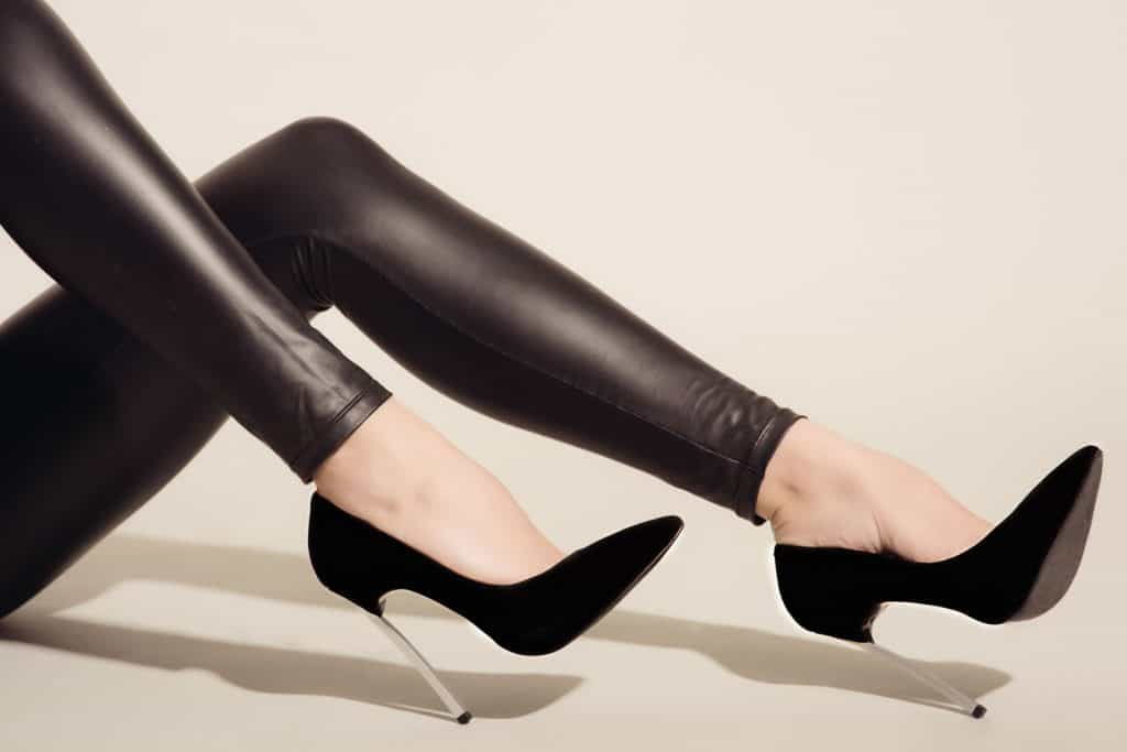 Women's legs in black tight-fitting leather trousers and high-heeled shoes sits on grey background.