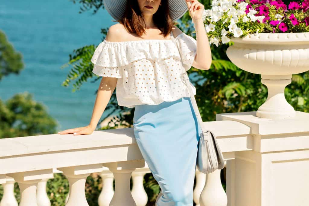 Young woman in a white blouse, blue pencil skirt and hat on a background of the sea horizon, What To Wear Under A Pencil Skirt?