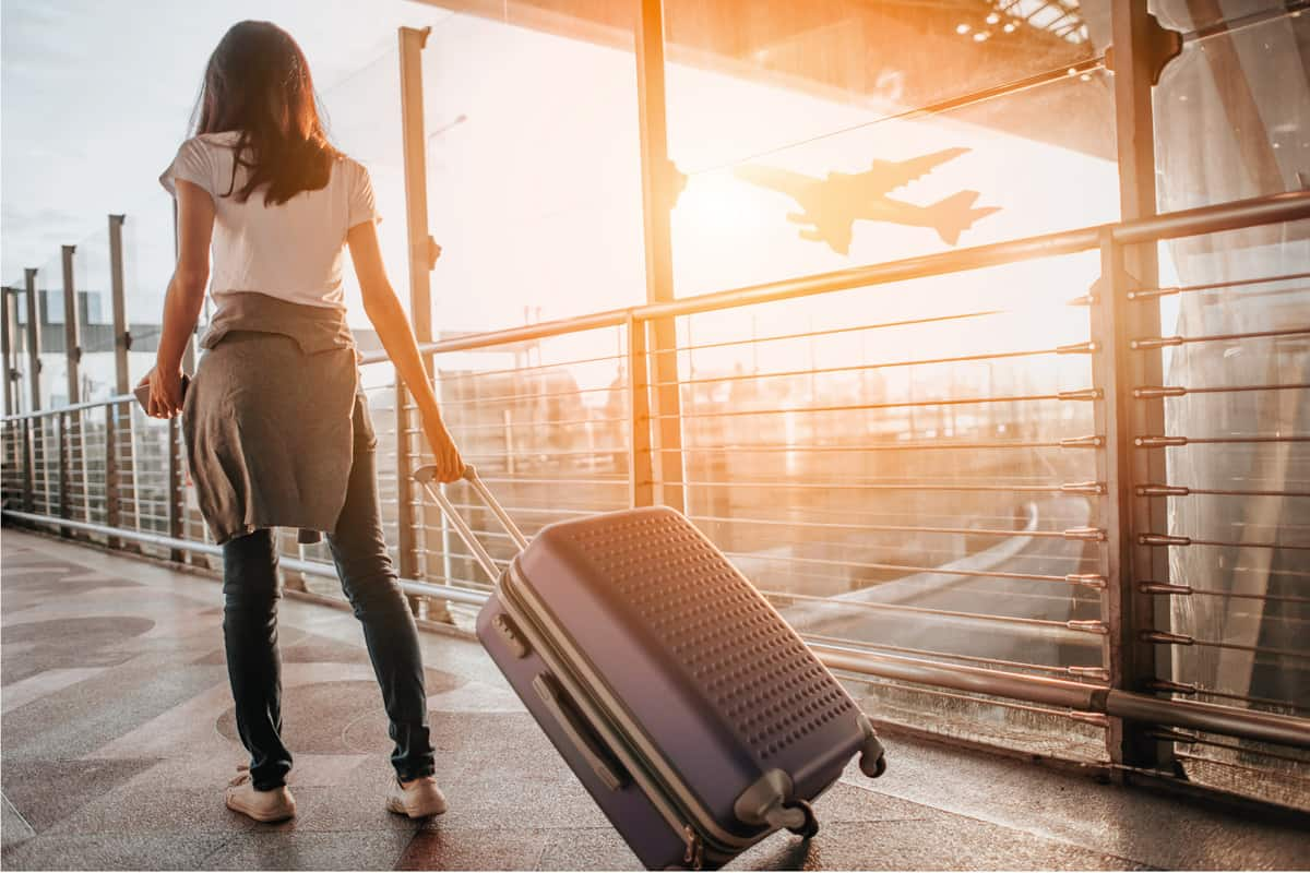 Young woman pulling suitcase in airport terminal
