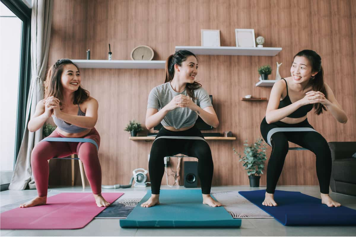 a group of asian chinese female friends practicing yoga in domestic living room together using laptop for online class
