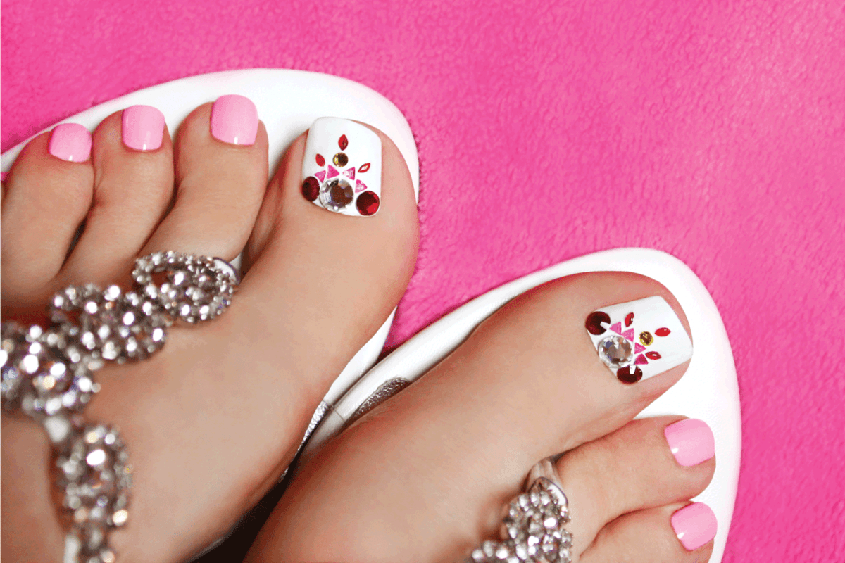 blinged out pedicure on toenails against pink background