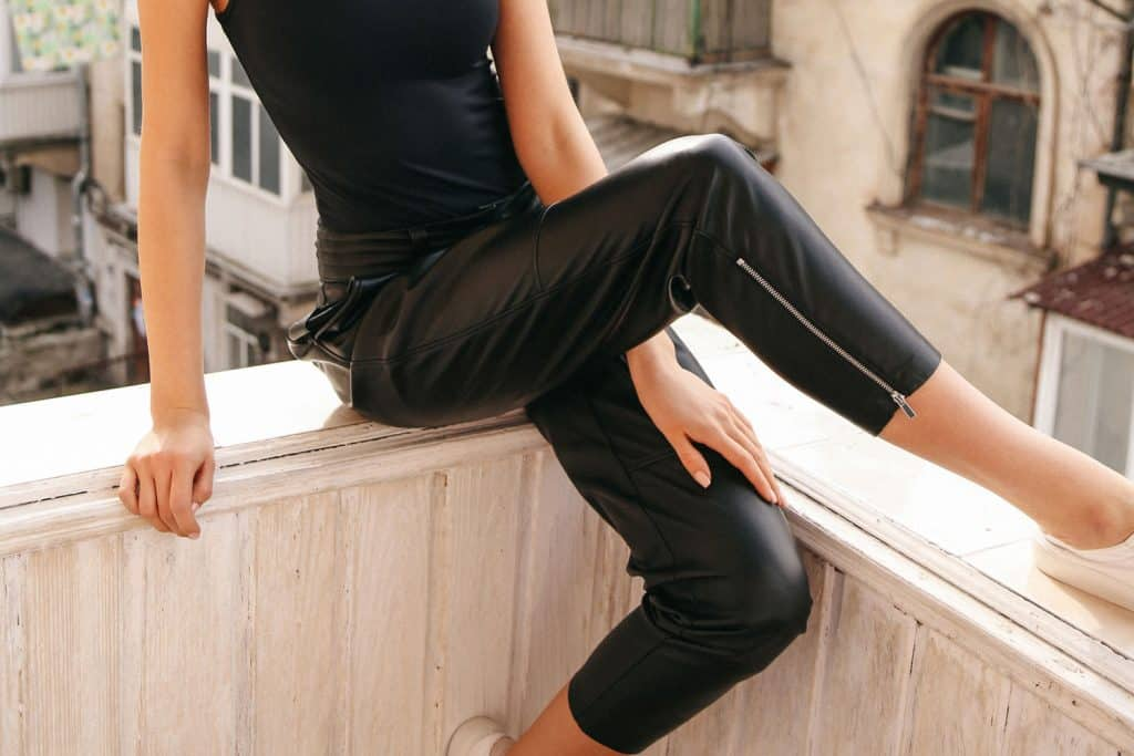 fashion photo of beautiful sexy woman with dark hair in elegant clothes posing in balcony with old city view on background wearing black leather jeans, How To Clean Leather Pants