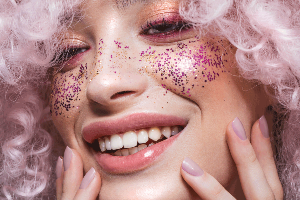 shot of a beautiful girl wearing curly pink wig and glitters on the cheeks. How To Get Body Glitter To Stick