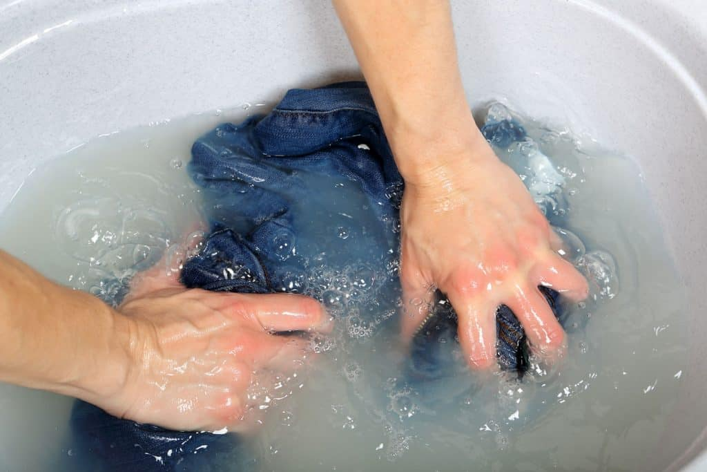 woman washing a pair of jeans by hand in plastic tub
