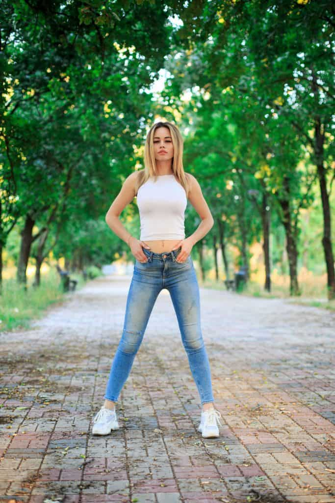A beautiful woman wearing a white top, blue jeans and white shoes on the park