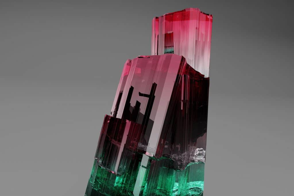 A gorgeous gradient colored formation of a tourmaline crystal on a gray background, How To Clean Tourmaline Jewelry