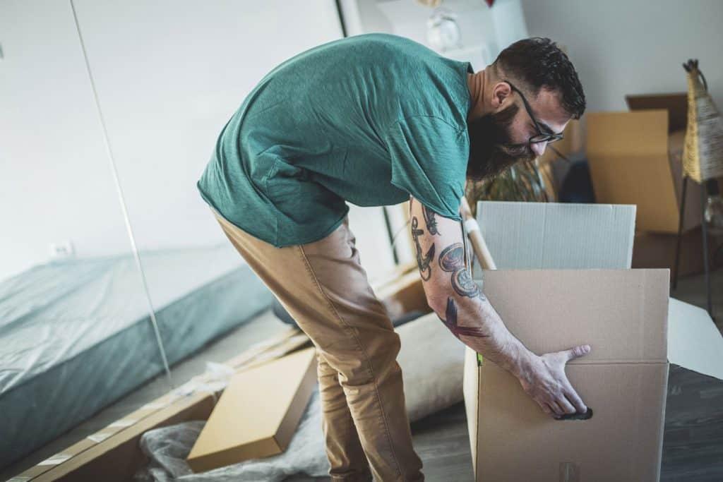 A man lifting a cardboard box while wearing a light green shirt and khaki pants