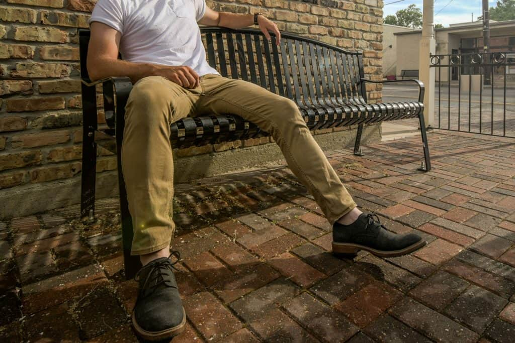 A man sitting on the bench wearing a white shirt and khaki pants, How Long Should Chino And Khaki Pants Be?