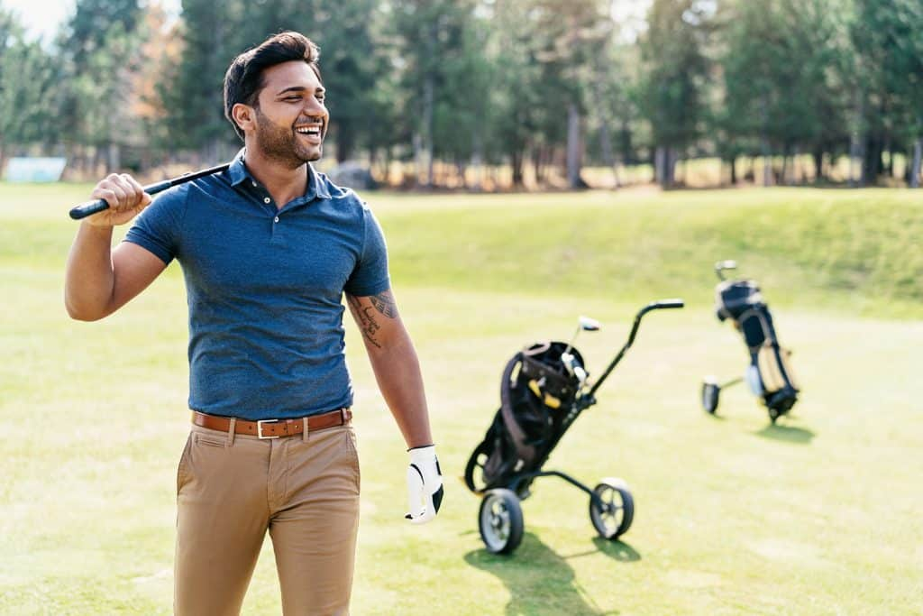 A man wearing a blue collar shirt and chino pants in his golf session