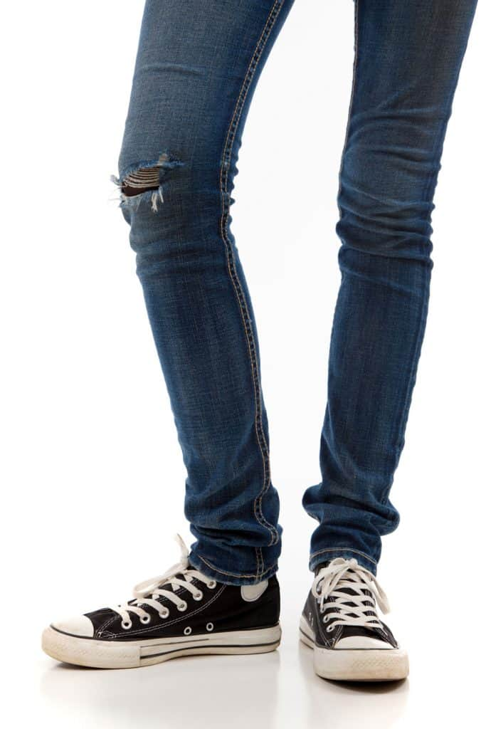 A man wearing blue jeans and sneakers on a white background
