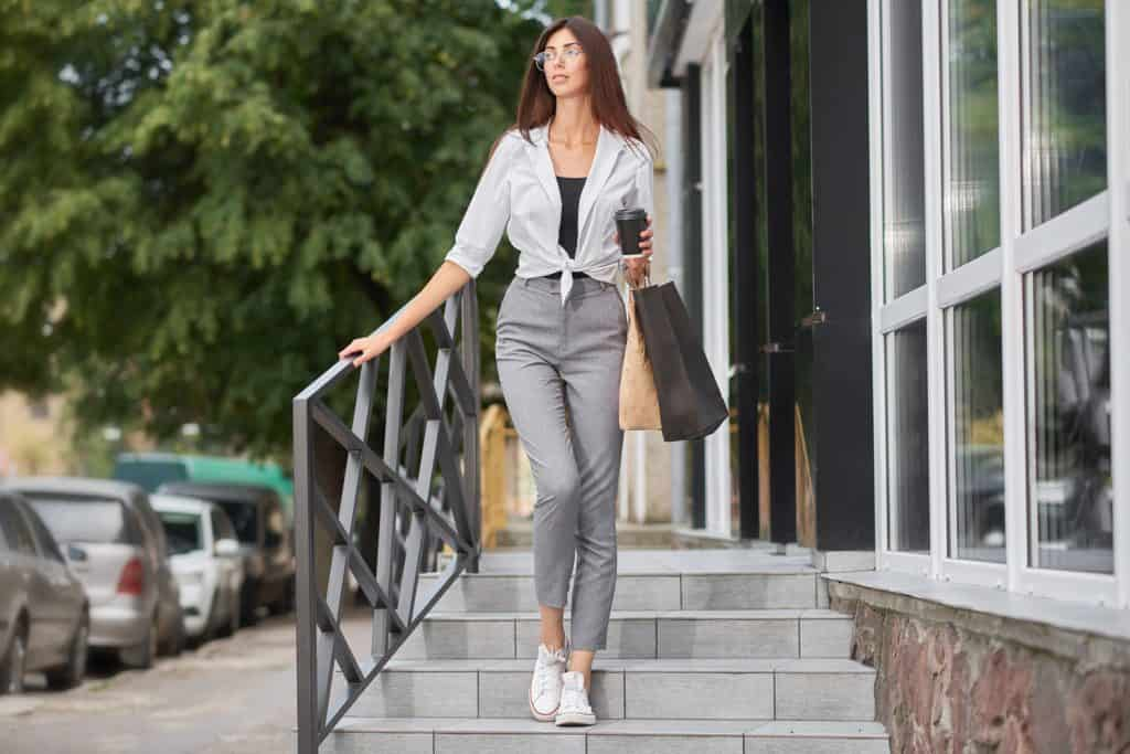 A tall beautiful woman wearing a white shirt gray pants and carrying a small paper bag