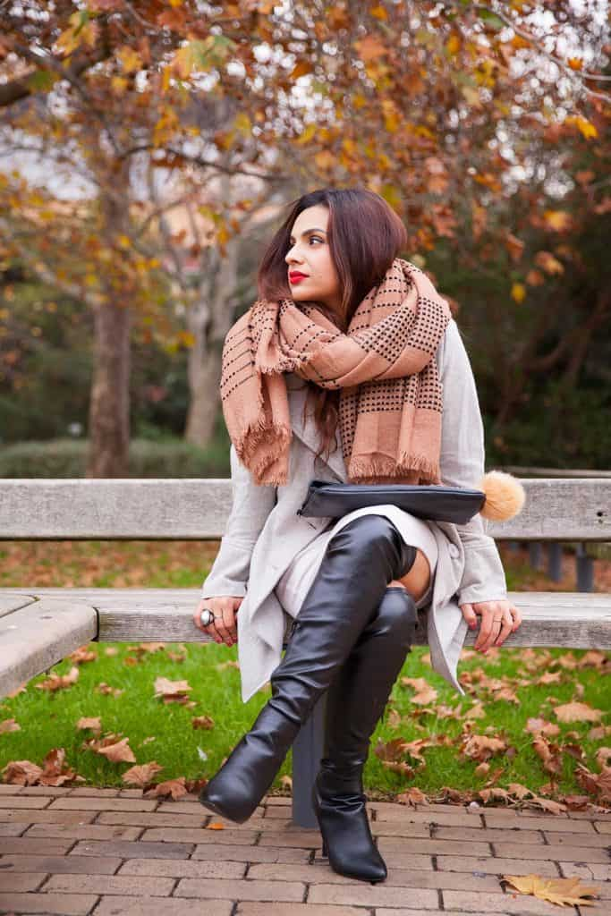 A well dressed young woman waits alone in the park