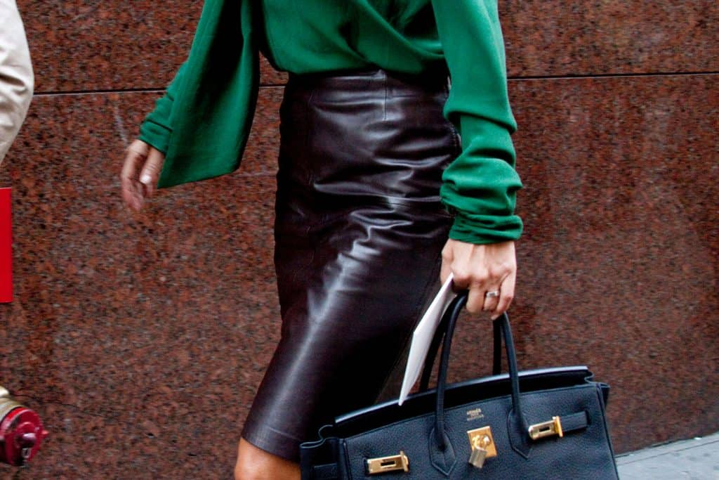 A woman dressed in pencil skirt and green casual blouse while walking in New York City, How Long Should A Pencil Skirt Be?