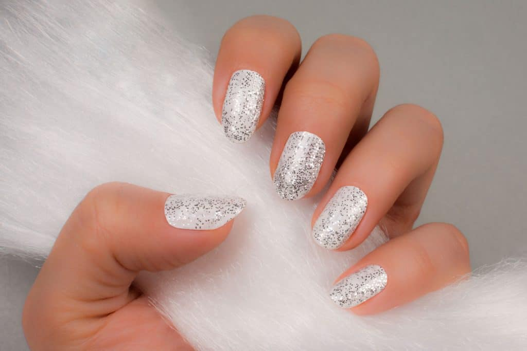 A woman holding furr showing her nails with gray glitter design