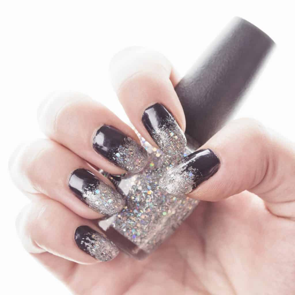 A woman holding gray glitter nails polish