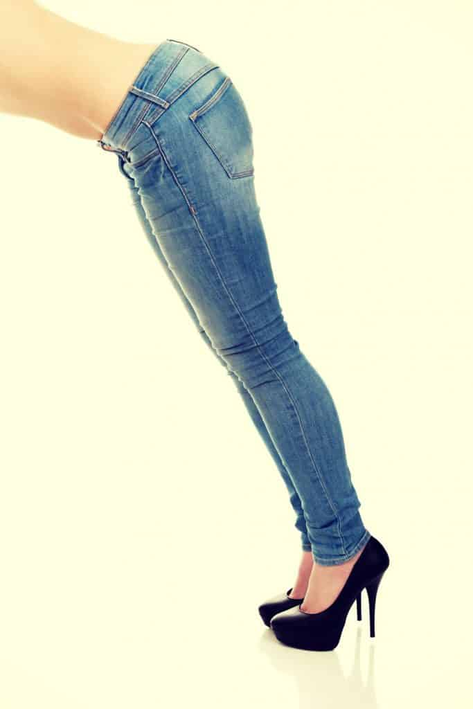 A woman leaning and wearing blue jeans on a beige background
