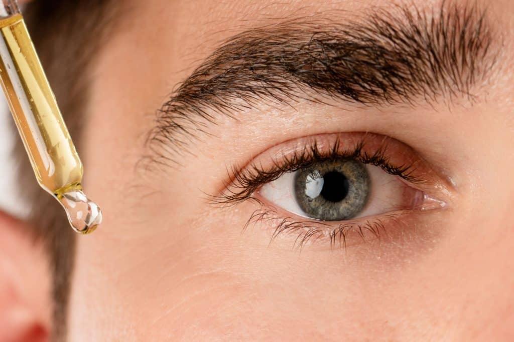 A woman putting eyelash serum