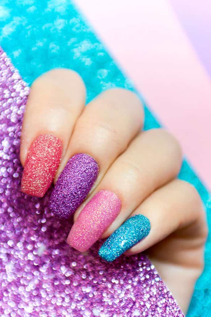A woman showing her multi-colored glitter finger nail designs