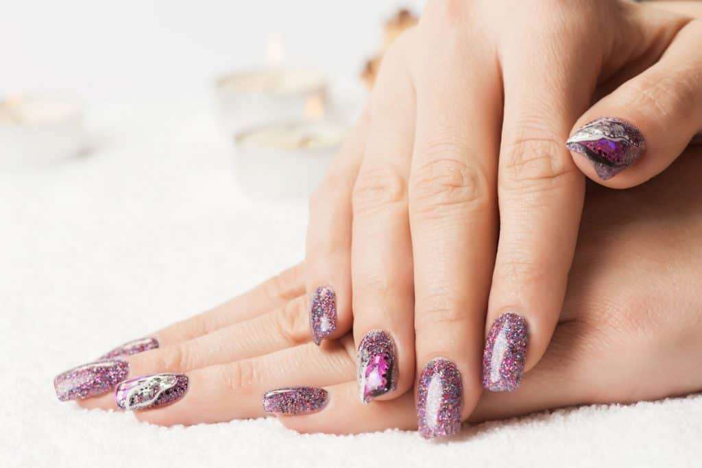 A woman showing her purple glitter designed nails, Can You Use Regular Glitter On Nails?
