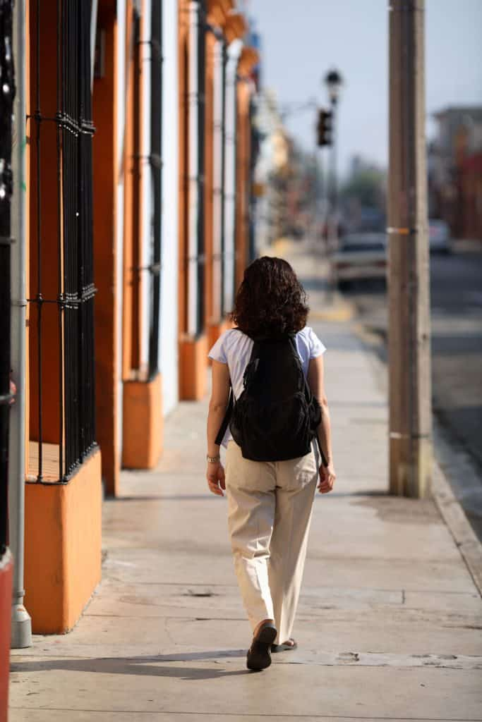 A woman walking on the street wearing a white shirt and khaki pants