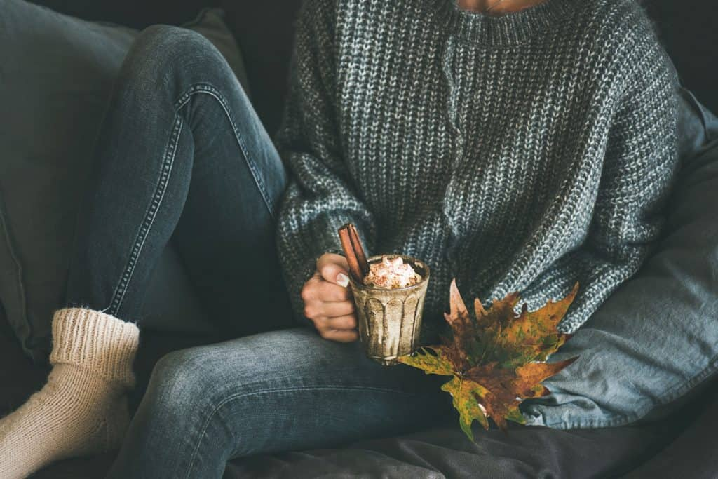 A woman wearing a gray sweater and holding a cup of hot chocolate