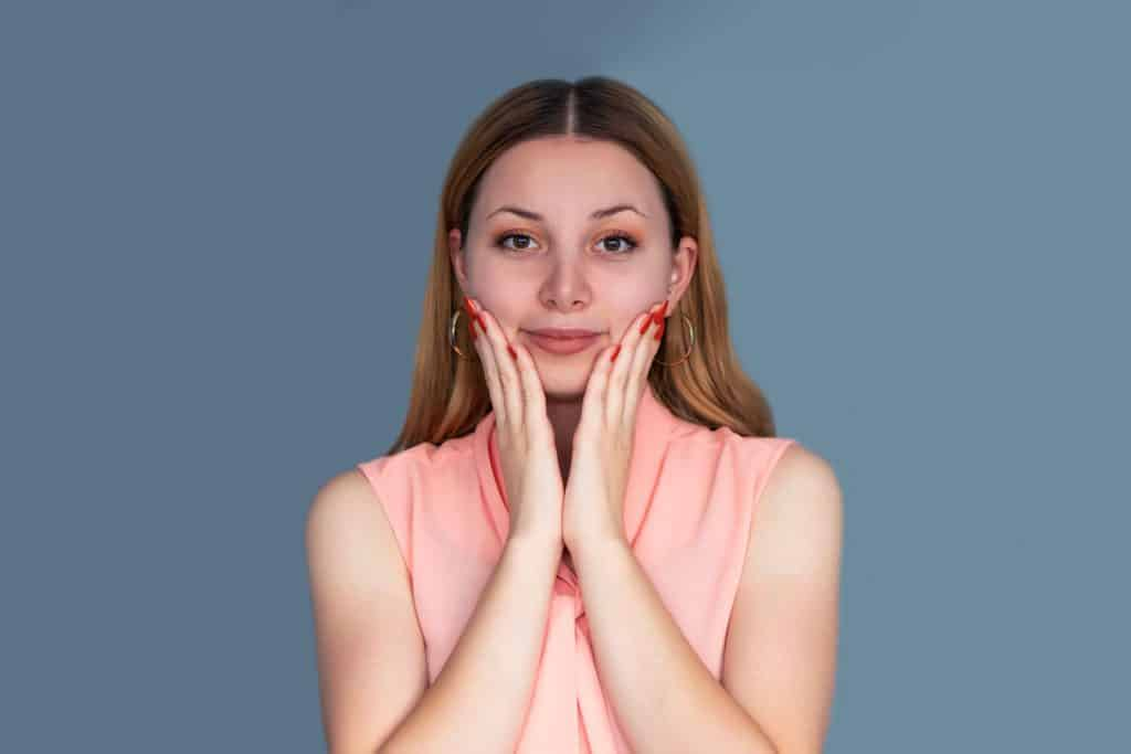 A woman wearing a pink sleeveless dress on a dark blue background, What Color Eyeshadow Goes With A Pink Dress Or Shirt?