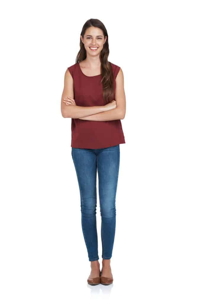 A woman wearing a red blouse and skinny blue jeans