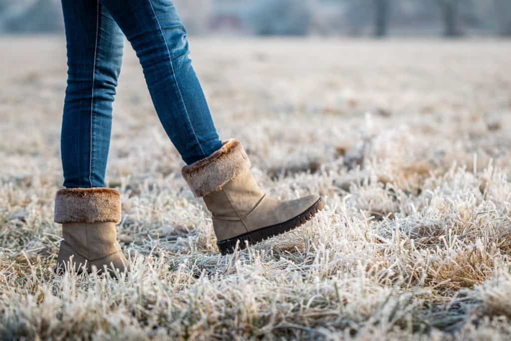 A woman wearing skinny jeans and winter boots walking on the field, Can You Wear Socks With Skinny Jeans?