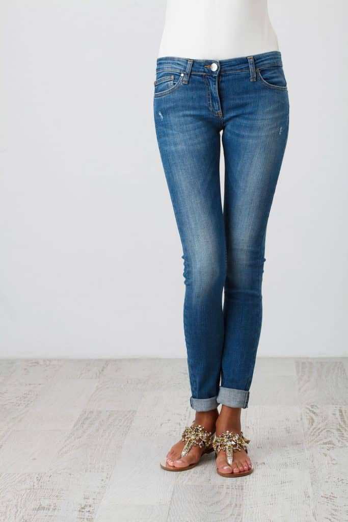 A woman wearing blue jeans and sandals inside her house