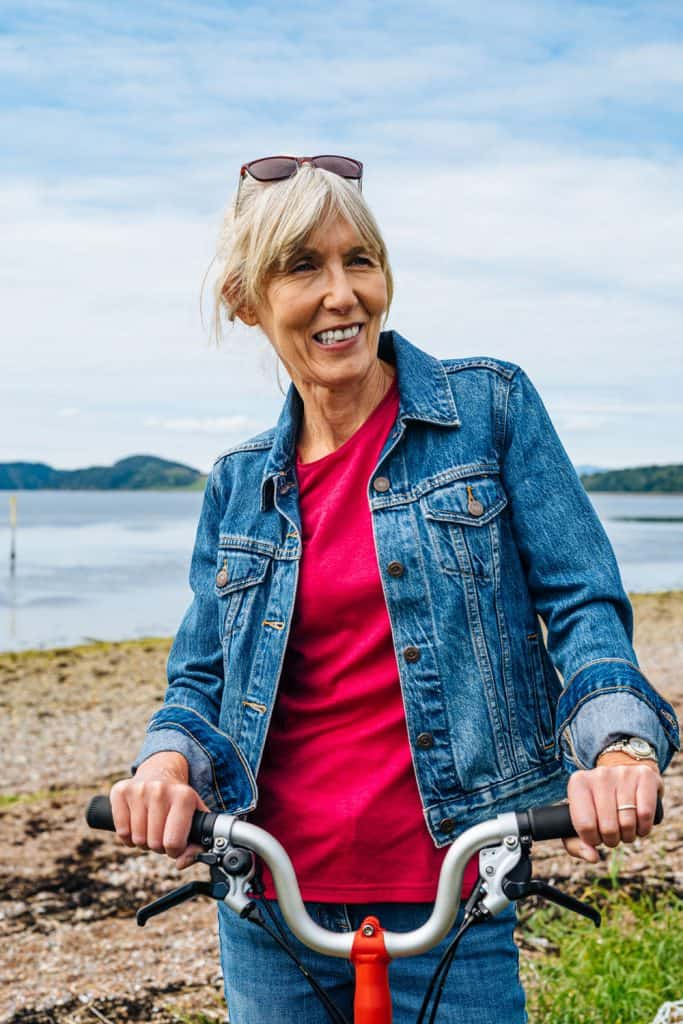 An elderly woman wearing a red shirt and denim jacket while riding her bike