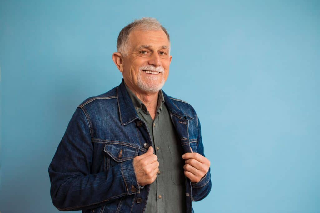 An elderly man tucking in his denim jacket for a photoshoot, How To Wear A Denim Jacket Over 50 [15 Awesome Ideas]